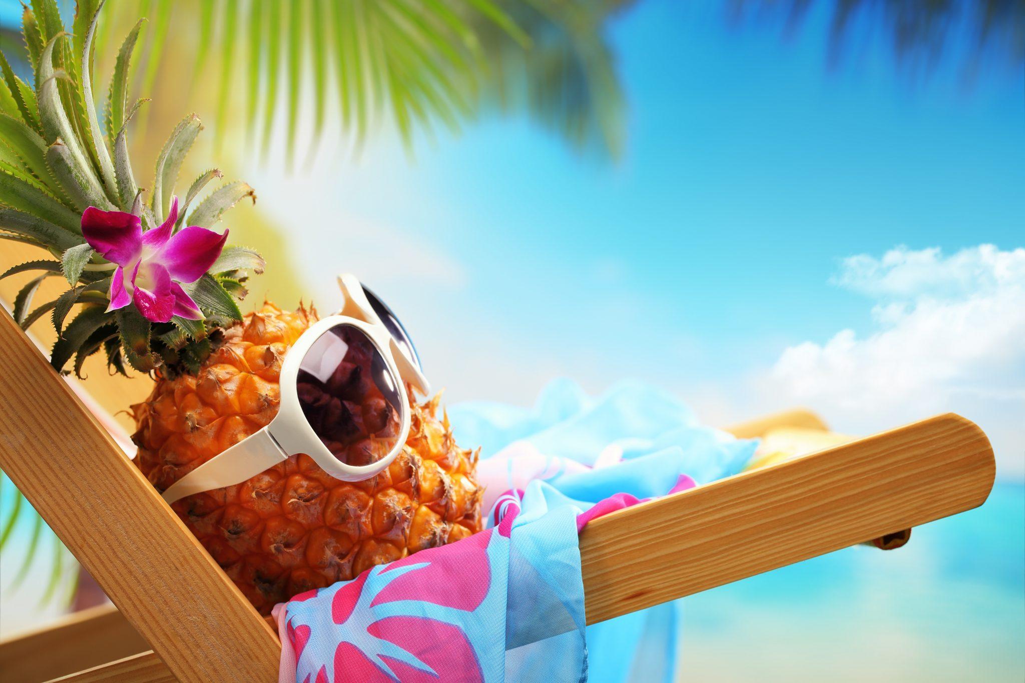 Ananas avec des lunettes de soleil sur une plage.